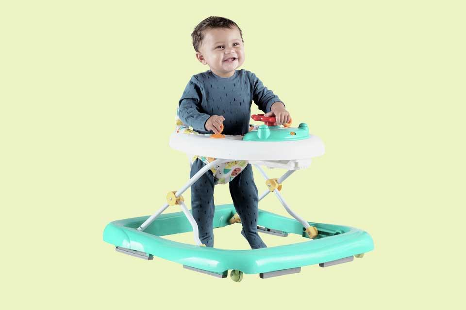 A smiling baby uses a green Chad Valley baby walker.