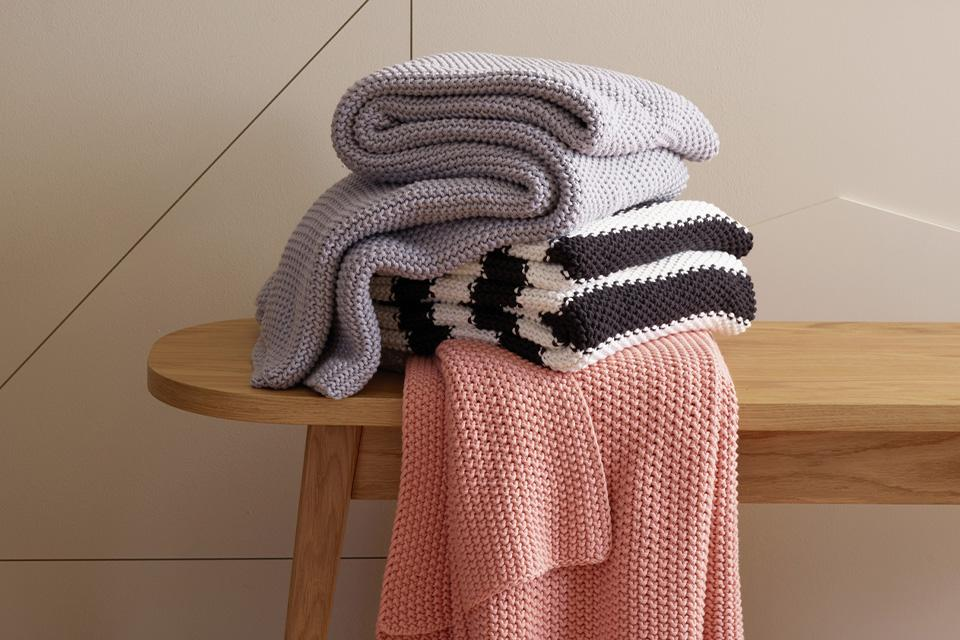 A folded pile of throws on a wooden bench.