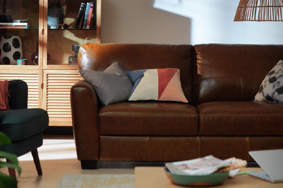 A brown leather sofa with mismatched accent cushions.