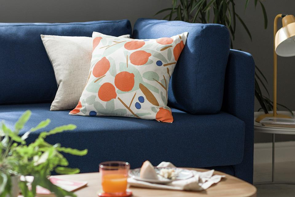 Patterned cushions on a blue velvet sofa.