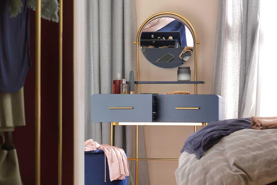Dark blue dressing table with round brass mirror and brass legs.