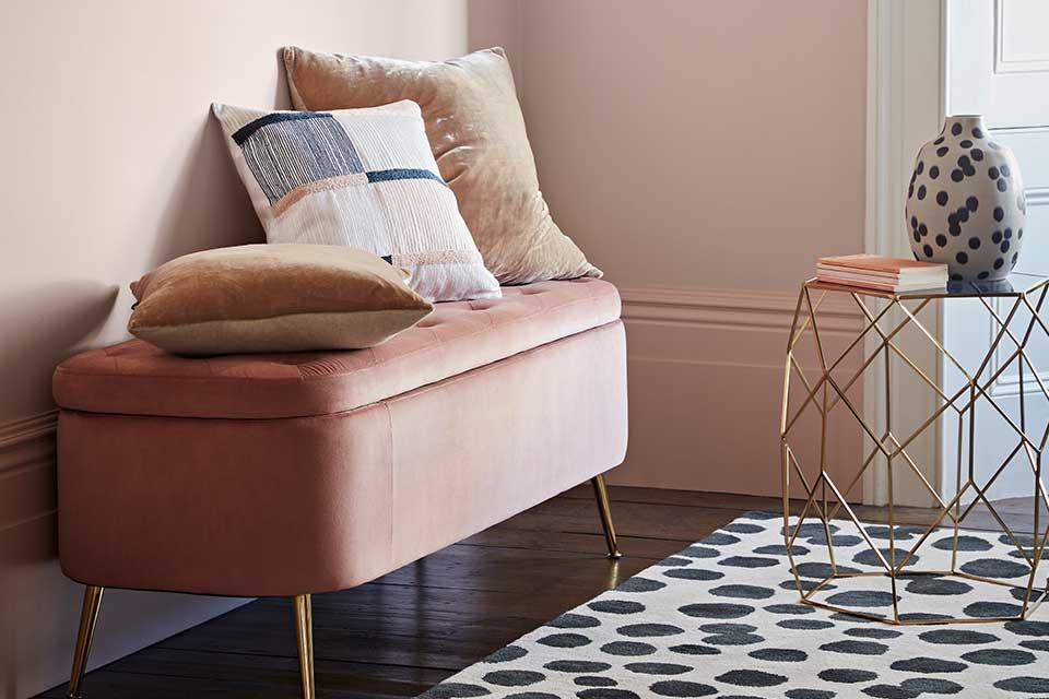 Pink velvet storage bench with cushions on top.