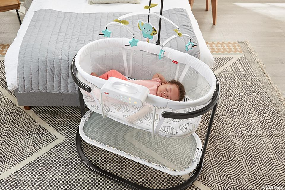 Baby asleep in fisher-price bassinet.