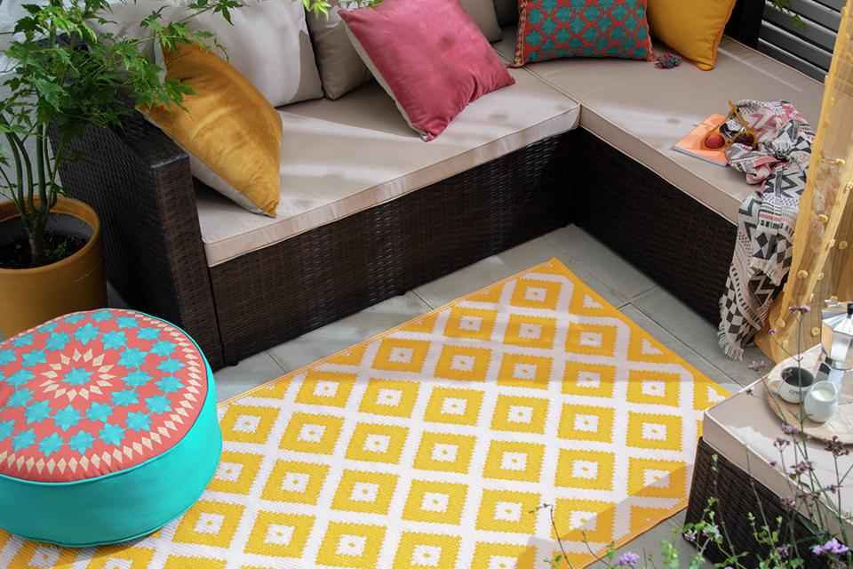 Yellow and white diamond print rug in garden.
