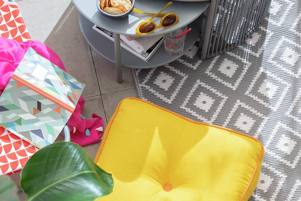 A yellow floor cushion on an outdoor rug.