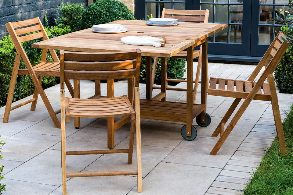 An image of a wooden table and chair set on a patio with surrounding flower beds.