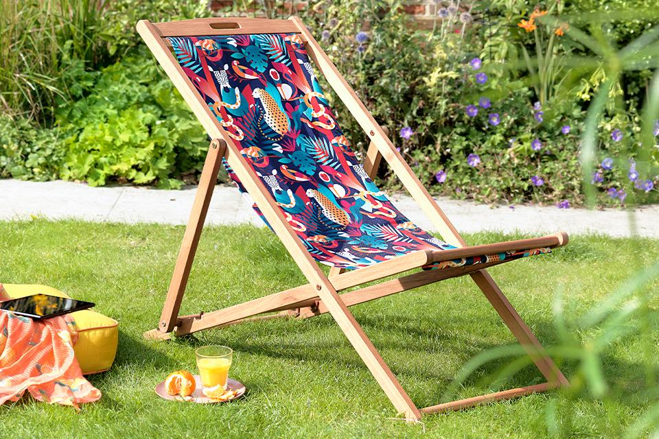 An image of a patterned deck chair next to a picnic on a lawn.