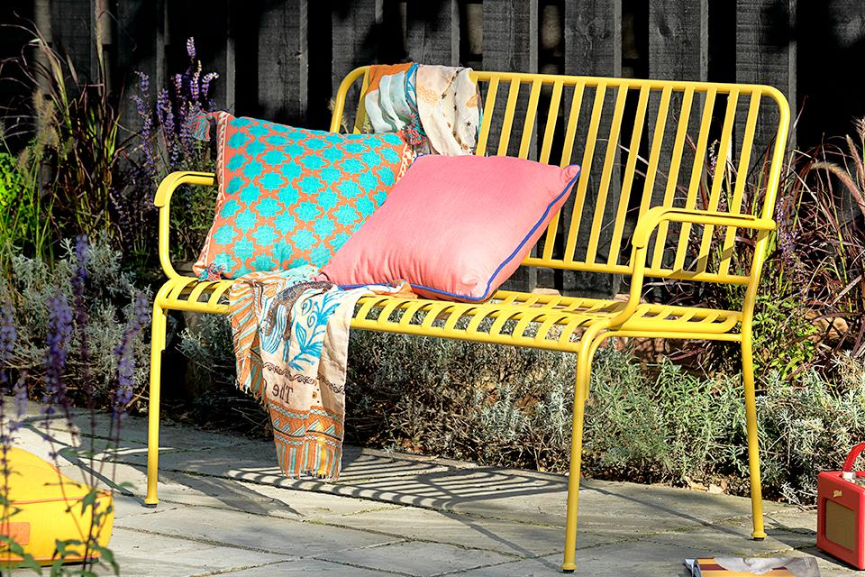 An image of a yellow bench with blue and pink cushions.