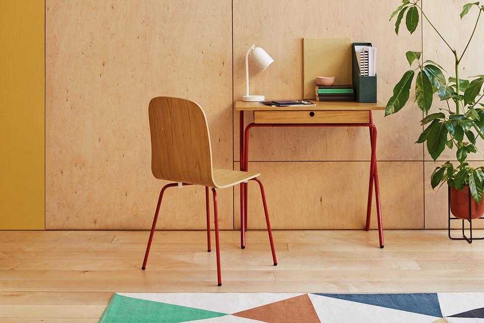 Image of a wooden desk with red legs against a beige wall.