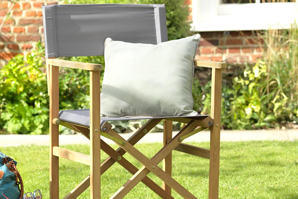 An image of a grey directors chair on a lawn with a cushion.