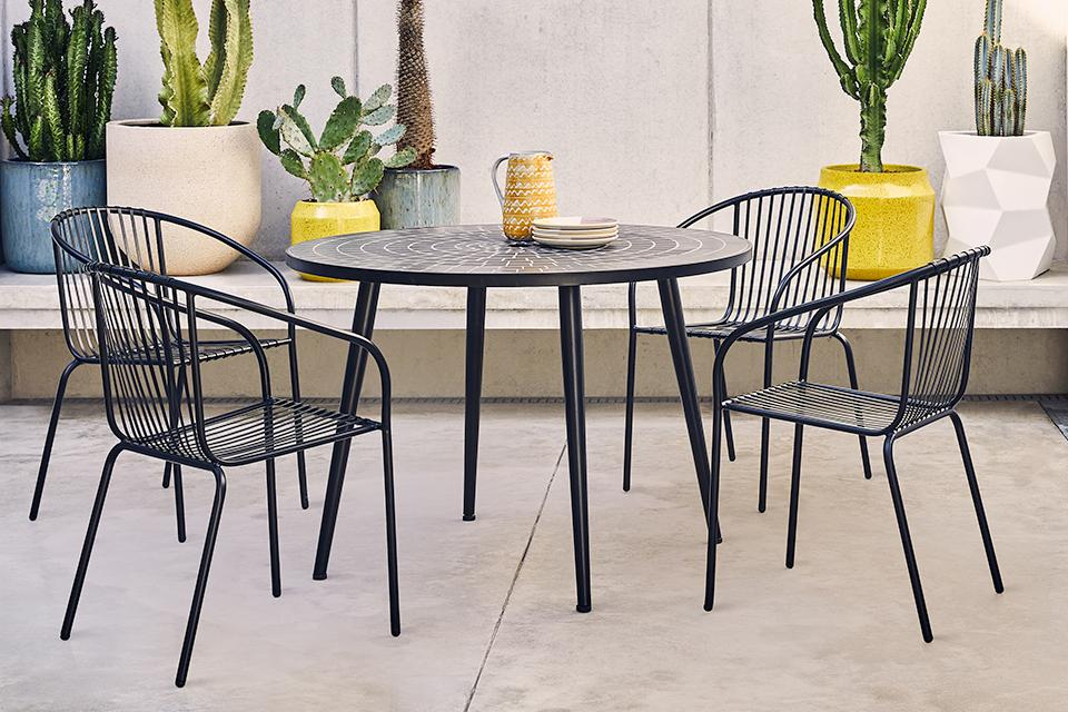 An image of a metal garden set with four chairs.
