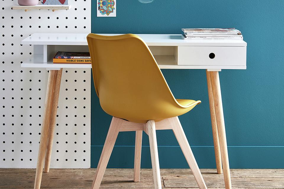 A yellow desk chair and white desk against a bright blue wall.