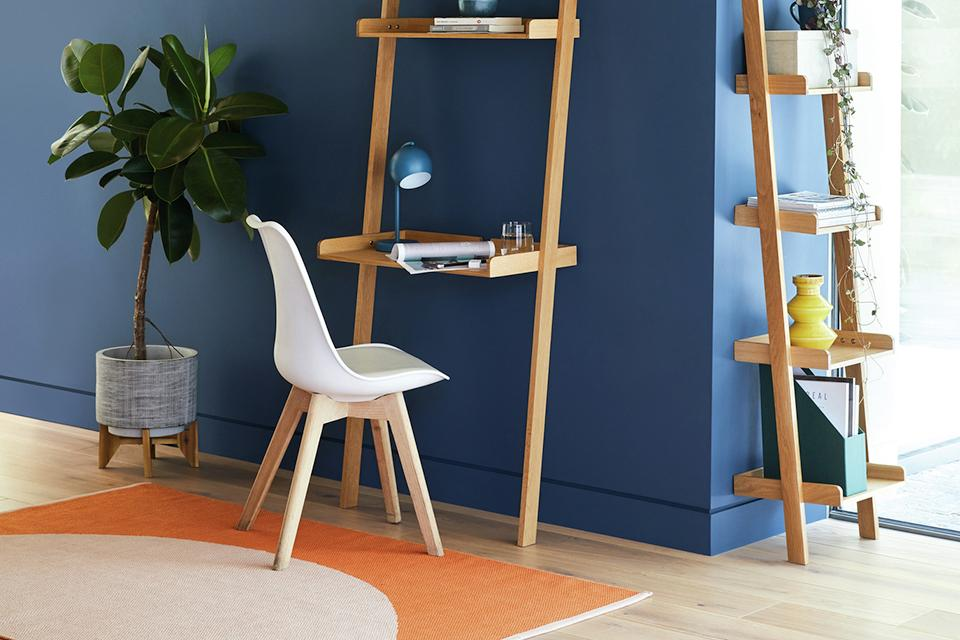 Image of a tall ladder style desk against a blue wall.