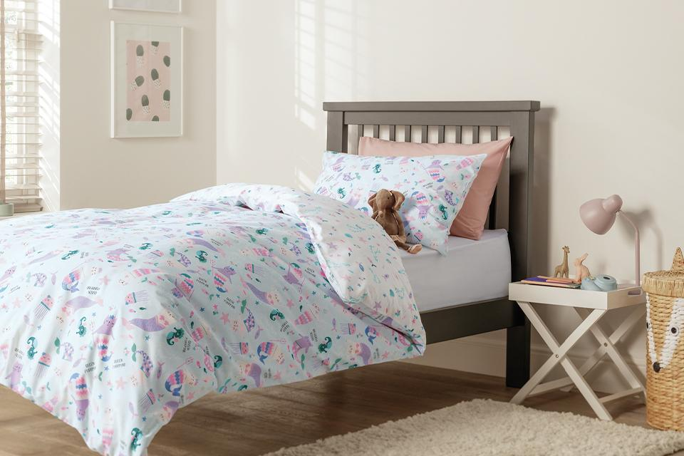 Image of a toddler size bed with an ocean theme bedding.