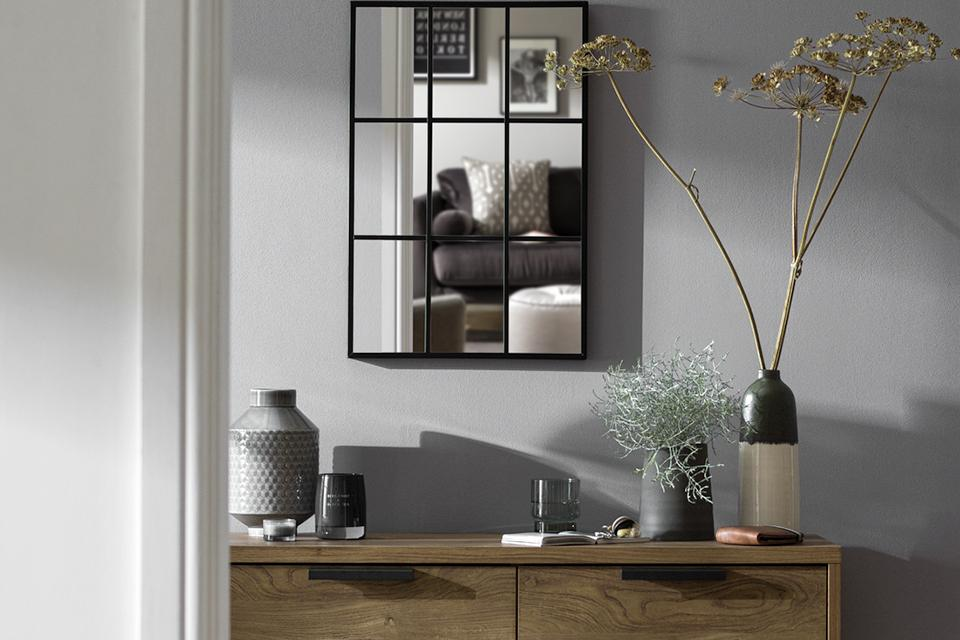 Window mirror hanging above dark oak sideboard.