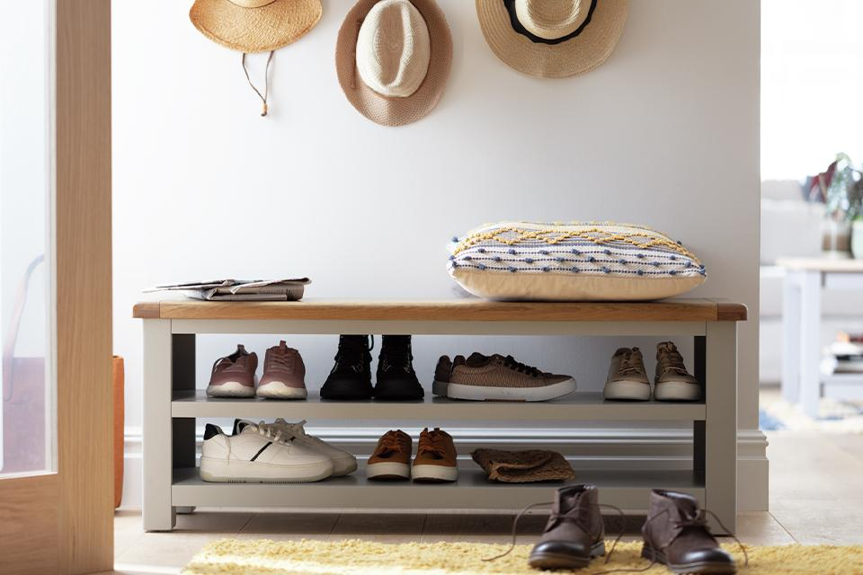 A white hallway with a grey and natural wood storage bench for shoes.