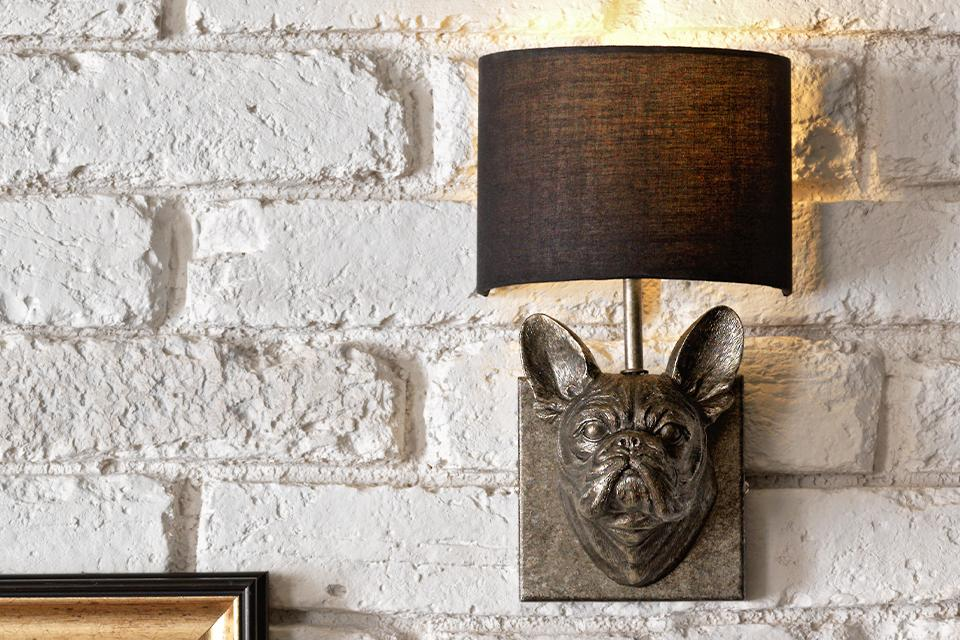 Image of a wall light with a dogs head as the lamp fixture with a grey lamp shade.