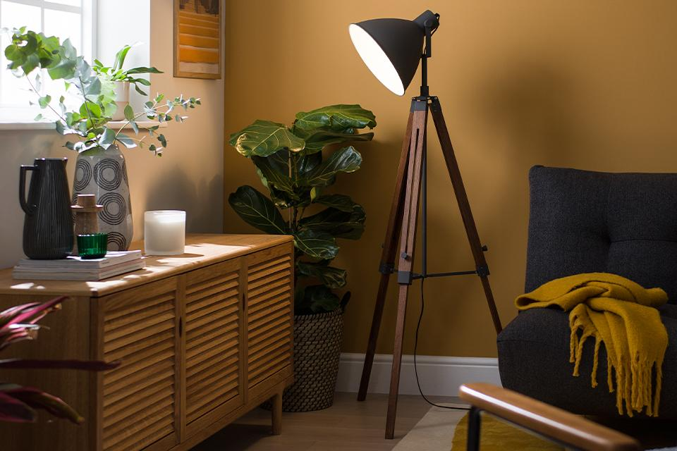 Image of a industrial style tripod floor lamp in a living room setting.