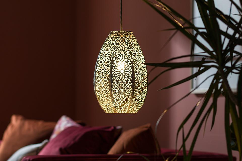 Image of a gold, Moroccan style pendant shade in a burgundy living room.