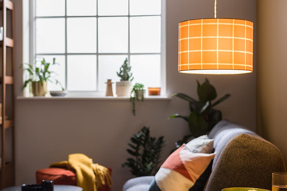 Image of a pendant light with a checked shade hanging next to a sofa.
