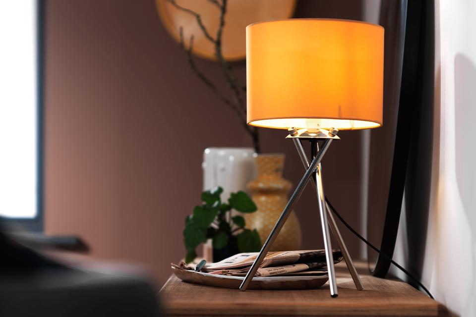 Image of a tripod table lamp with chrome legs and an orange shade.