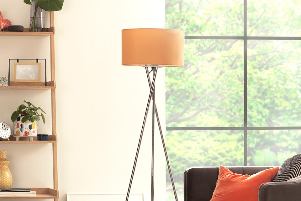 Image of a tripod style floor lamp white chrome legs and and orange shade.