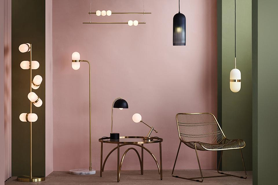 Image of a selection lighting types in gold and black in a pale pink room.