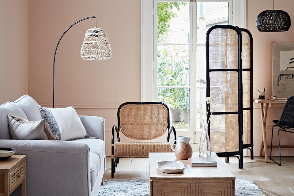 A pale pink living room with a white rattan floor lamp.
