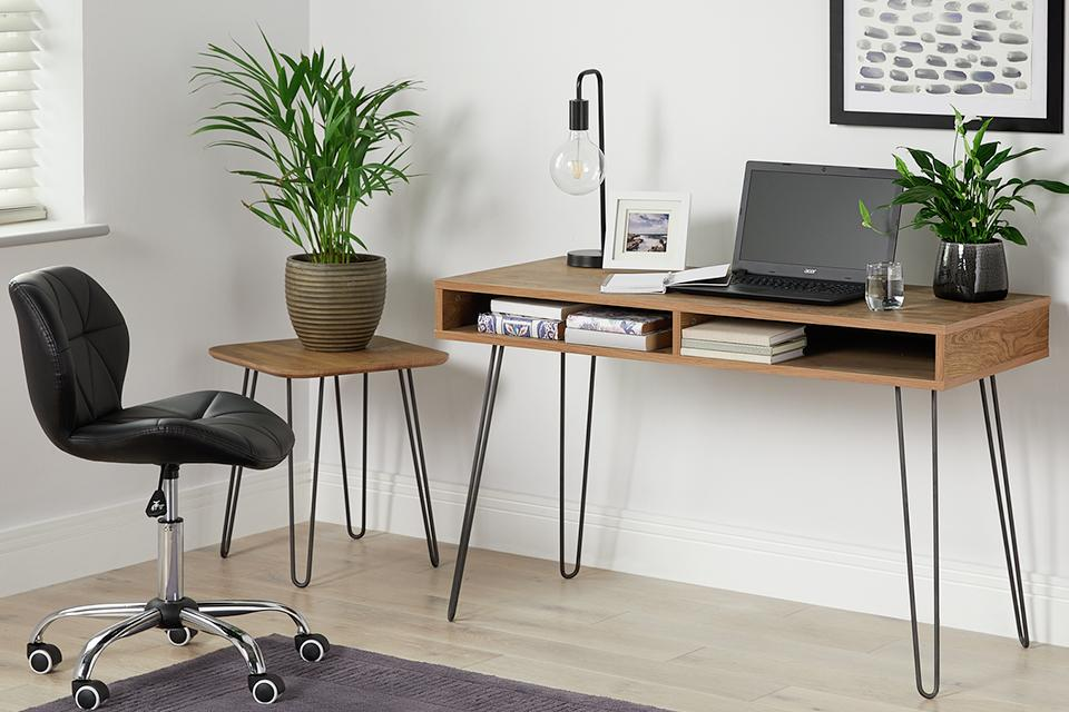 Wooden desk with metal legs and matching side table with a black office chair on wheels.