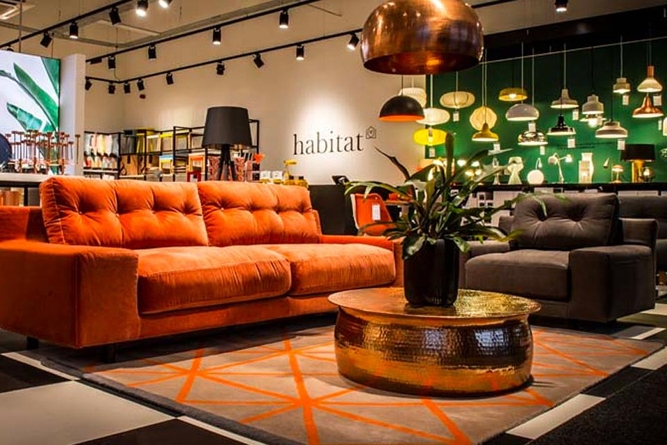 Orange sofa and gold round table in store.