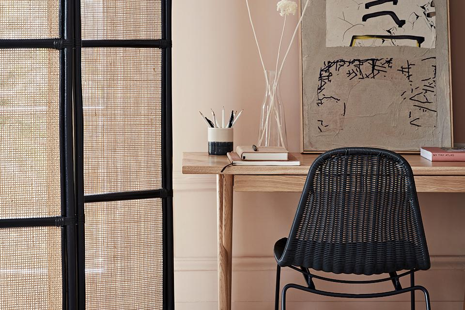 A black rattan chair beneath a wooden desk in a dusky pink room.