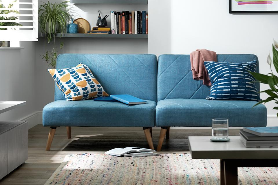 Image of a blue sofa bed in a white living room.