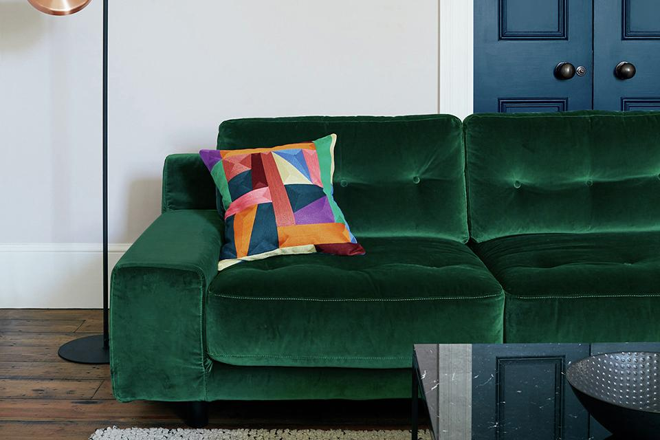 Image of a green velvet sofa with multicoloured cushion in living room.