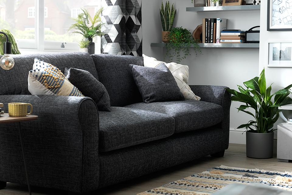 Image of grey sofa with cushions in living room.