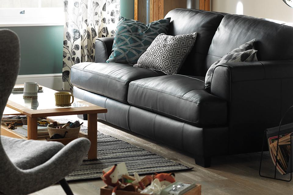 Image of black leather sofa with cushions in lounge.