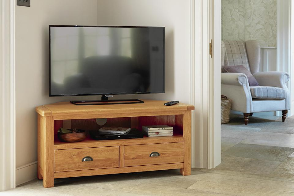 Image of a wooden corner TV stand in a pale blue living room..