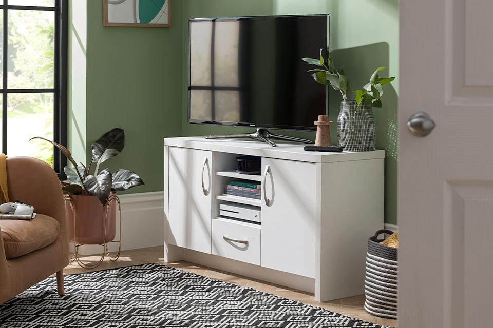 Image of a white TV stand and sideboard combo in a green living room.