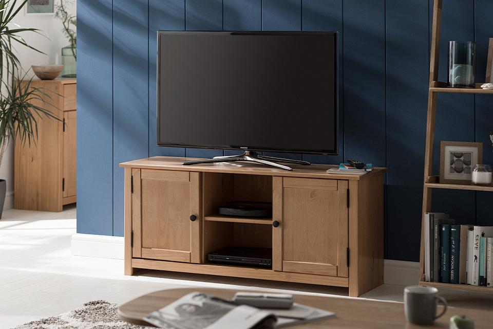 Image of a wooden TV stand with drawers in a dark blue living room.