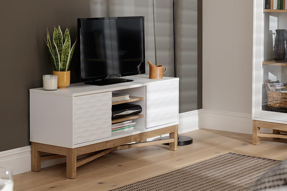 Image of a white TV stand in a grey living room.
