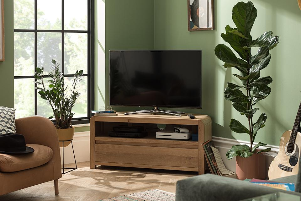 Image of a wooden corner TV stand in a green living room.