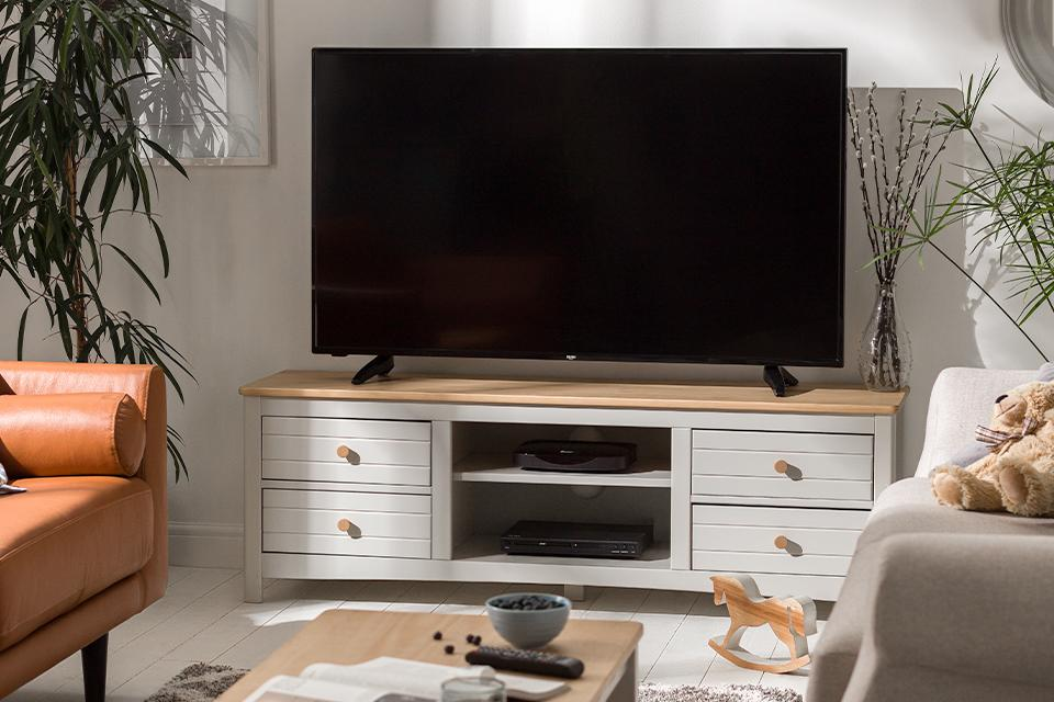Image of a off-white TV stand with a wooden top in a white living room.