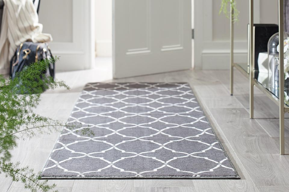 White and grey geometric runner placed in entrance way with sideboard on the right and indoor plant and chair on the left.