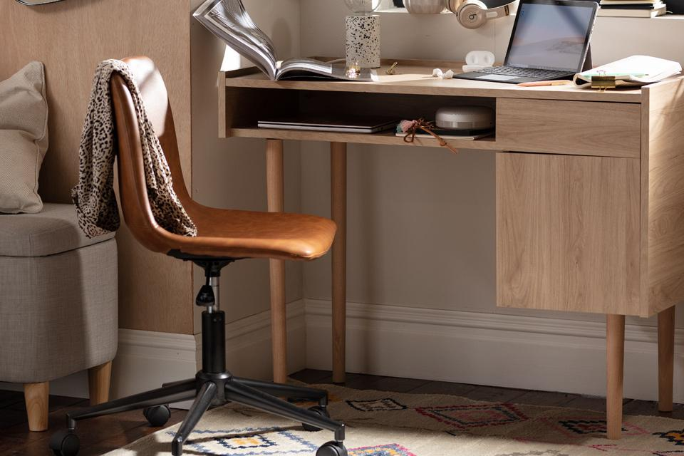 Home office with oak storage desk and open bookcase with accessories.