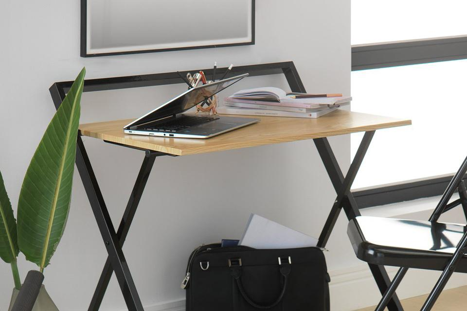 Folding desk with oak top and black metal legs.