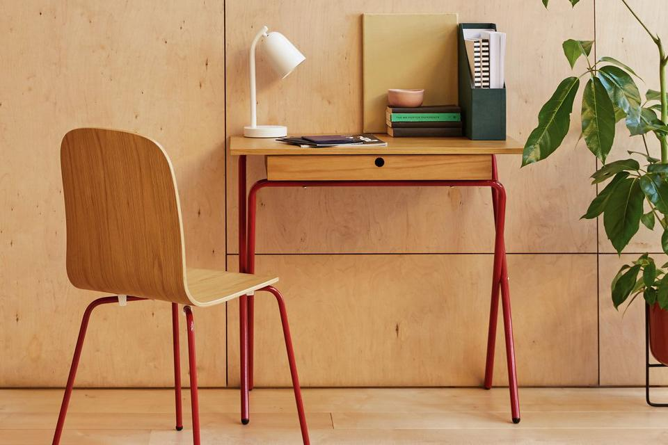 small oak desk and chair with red legs.