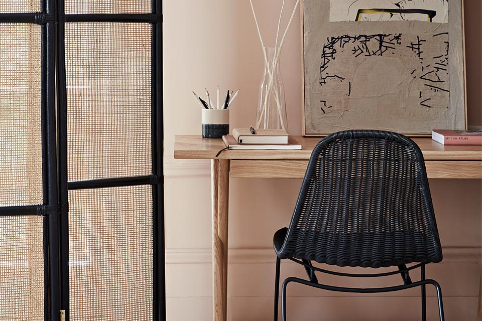 Rattan chair and screen divider in home office.