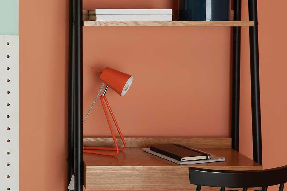 Orange Habitat Lizzie desk lamp on a ladder desk.