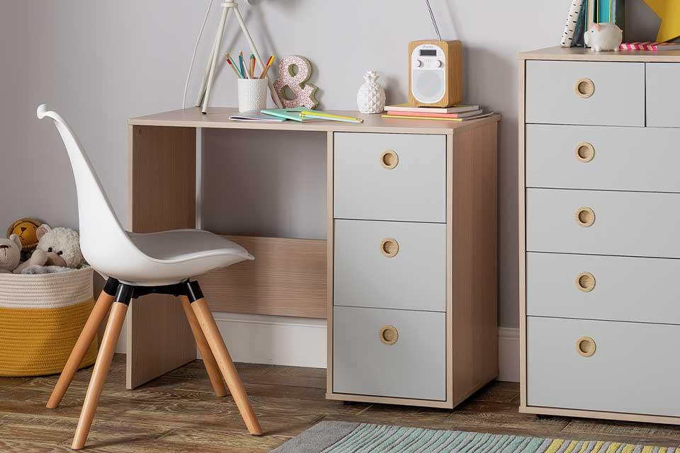 Two tone light grey and wood desk with matching chest of drawers and a desk chair, in a child's bedroom setting.