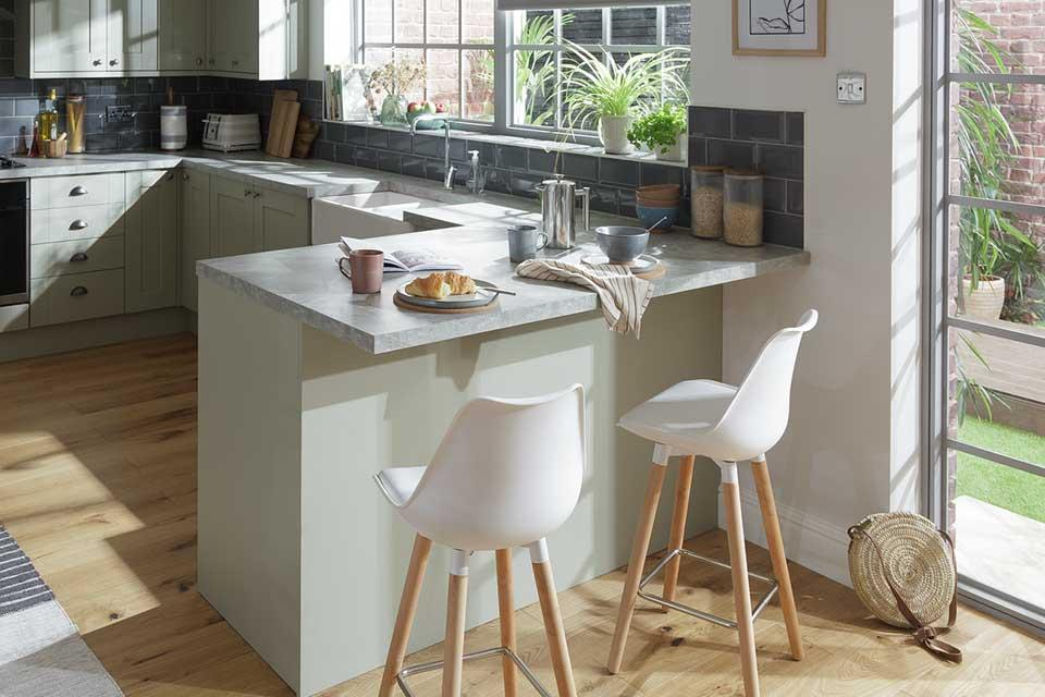 A modern and bright kitchen with a breakfast bar and two white bar stools.
