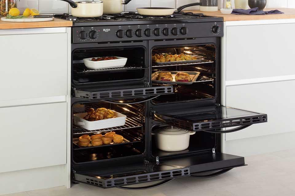 A range cooker with open doors showing lots of food inside and saucepans on top